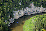 Two rafts of fishermen on the Smith River in Montana beneath rock walls along the shore