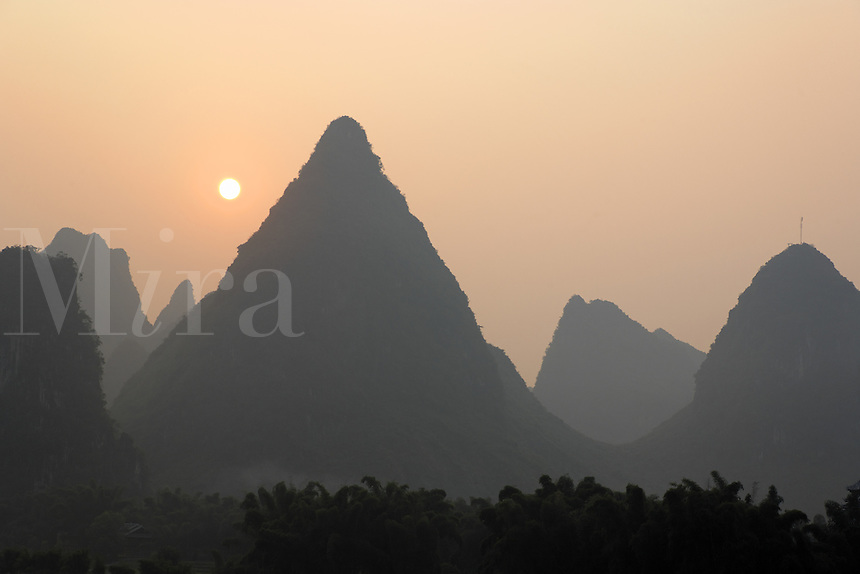 Sun rising over karst mountains, Yangshuo, Guanxi, China