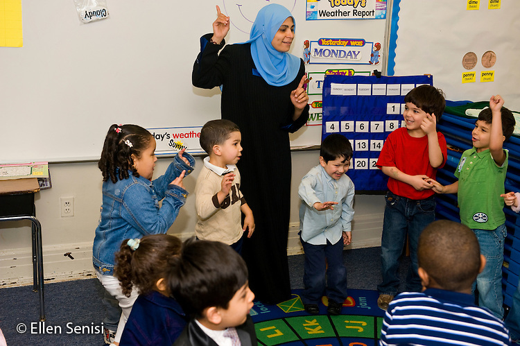 MR / Jersey City, NJ.Al-Ghazaly Elementary School (private Islamic school with a curriculum that follows state curriculum content standards and also teaches Islamic studies) / Pre-K classroom.Teacher (Egyptian-American) and students bend and move together to music at group time..ID: AI_gPag  MR: AI_gPag.© Ellen B. Senisi