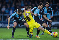 Matt Bloomfield of Wycombe Wanderers & Sam Wood of Wycombe Wanderers battle with Chris Maguire of Oxford United during the Sky Bet League 2 match between Wycombe Wanderers and Oxford United at Adams Park, High Wycombe, England on 19 December 2015. Photo by Andy Rowland.