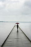 walking on a pier looking out over the water on a grey rainy day