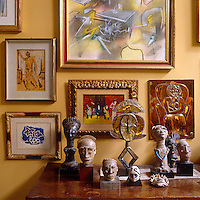 Close up of 20th century paintings and ethnic sculptures