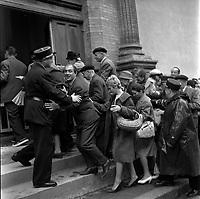 """Affaire de la """"Tournerie des drogueurs""""  JUIN 1961<br /> <br /> Devant le Palais de Justice, rue des Fleurs. 5 juin 1961. Plan moyen de la foule entrant dans le palais de justice, des policiers calment les personnes. Cliché pris dans le cadre de l'affaire de la """"Tournerie des drogueurs"""" dont le procès s'est ouvert à Toulouse le 5 juin 1961. Observation: Affaire de la """"Tournerie des drogueurs"""" : Procès qui s'est ouvert aux assises de Toulouse le 5 juin 1961, sous la présidence de M. Gervais (conseiller doyen). Sur le banc des accusés se trouvent François Lopez, Raoul Berdier, Marie-Thérèse Davergne (Maïté) et d'autres malfaiteurs toulousains (Camille Ajestron, Henri Oustric, Raymond Peralo, Marcel Filiol, Paul Carrère, Charles Davant et François Borja). Outre les accusations pour association de malfaiteurs, ils comparaissent pour l'assassinat de Jean Lannelongue, propriétaire du Cabaret la Tournerie des Drogueurs (rue des Tourneurs) dans la nuit du 3 au 4 janvier 1959, au cours d'une tentative de racket."""