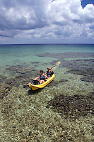 Two women (MR) with dive equipment paddling a kayak over a shallow reef in Cayman Brac, Cayman Islands