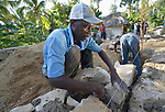 Yves Elkine places stones in the foundation of a house being built by Church World Service for a family that lost their home in Lareserve, a village near Jean-Rabel in northwestern Haiti, during Hurricane Matthew in 2016.  <br /> <br /> CWS is a member of the ACT Alliance.