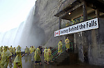 Niagara Falls, Ontario, Canada - 01 August 2006---Tourists / visitors equipped with yellow plastic coats against the mist at the entrance to the Journey Behind the Falls (Horseshoe Falls, on the Canadian side) ---nature, people, tourism---Photo: © HorstWagner.eu