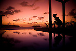 A young girl admires the reflections of a sunset in a pool.