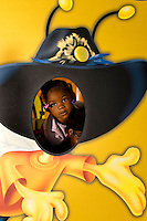 A young girl sticks her head into a cutout of a cowboy hat at Food Lion Speed Street in uptown Charlotte, NC.