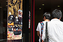 Customers walk pass an advertisement of the Burger King's new black burgers on display outside the Shinjuku store on August 21, 2015, Tokyo, Japan. The chain's two new black burgers use bamboo charcoal-infused buns and cheese, Black Hashed Sauce (a mix of red wine, squid ink, onions, tomato and crushed garlic), and slices of grilled eggplant. In July Burger King launched two red burgers in another Japan only colored burgers promotion. The two new black burgers are the Kuro Shogun costing 690 JPY (5.59 USD) and the Kuro Taisho costing 590 JPY (4.78 USD). They will be on sale for a limited time in Burger King's Japanese stores from August 21st. (Photo by Rodrigo Reyes Marin/AFLO)