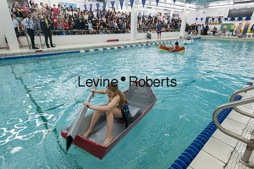 "Vera Linani, a freshman, a senior, pilots his team's boat to victory in Brooklyn Technical High School's Cardboard Boat Regatta in the school's pool in Brooklyn in New York on Friday, March 1, 2013. As part of Engineering Week the teams of students constructed boats made only of cardboard and duct tape. The team's assigned ""captain"" piloted their boat from one end of the pool to the other and back in a heat with other boats, hopefully without sinking. The surviving boats were timed and the winners received bragging rights with an award also going to the most spectacular sinking. (© Richard B. Levine)"