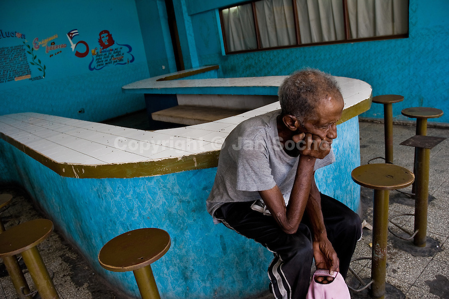An old Cuban man sits at an empty lunch counter in Santa Clara, Cuba, 8 August 2008. About 50 years after the national rebellion, led by Fidel Castro, and adopting the communist ideology shortly after the victory, the Caribbean island of Cuba is the only country in Americas having the communist political system. Although the Cuban state-controlled economy has never been developed enough to allow Cubans living in social conditions similar to the US or to Europe, mostly middle-age and older Cubans still support the Castro Brothers' regime and the idea of the Cuban Revolution. Since the 1990s Cuba struggles with chronic economic crisis and mainly young Cubans call for the economic changes.