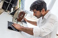 """Das Berliner Start-up """"mimycri"""" produziert Taschen aus den Gummiplanen gestrandeter Fluechtlingsboote.<br /> Statt Griechenlands Straende im Muell der gestrandeten Fluechtlingsboote ersticken zu lassen, stellt das Berliner Unternehmen """"mimycri"""" daraus Taschen und Rucksaecke her und bietet Fluechtlingen eine Chance auf Normalitaet und Regelmaessigkeit.<br /> Im Bild: Abid Ali, gefluechteter Schneider aus Pakistan bei der Arbeit.<br /> 8.8.2017, Berlin<br /> Copyright: Christian-Ditsch.de<br /> [Inhaltsveraendernde Manipulation des Fotos nur nach ausdruecklicher Genehmigung des Fotografen. Vereinbarungen ueber Abtretung von Persoenlichkeitsrechten/Model Release der abgebildeten Person/Personen liegen nicht vor. NO MODEL RELEASE! Nur fuer Redaktionelle Zwecke. Don't publish without copyright Christian-Ditsch.de, Veroeffentlichung nur mit Fotografennennung, sowie gegen Honorar, MwSt. und Beleg. Konto: I N G - D i B a, IBAN DE58500105175400192269, BIC INGDDEFFXXX, Kontakt: post@christian-ditsch.de<br /> Bei der Bearbeitung der Dateiinformationen darf die Urheberkennzeichnung in den EXIF- und  IPTC-Daten nicht entfernt werden, diese sind in digitalen Medien nach §95c UrhG rechtlich geschuetzt. Der Urhebervermerk wird gemaess §13 UrhG verlangt.]"""