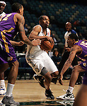 Zach Graham, of the Reno Bighorns, drives past Los Angeles D-Fenders Malcolm Thomas, left, and Brian Hamilton during the men's basketball game, in Reno, Nev., on Friday, Jan. 6, 2012. The De-Fenders won 109-78..Photo by Cathleen Allison