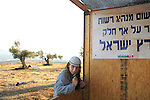 A young settler and a shack, in the unauthorized Israeli outpost of Ramat Migron, West Bank.