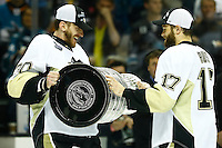 Matt Murray #30 hands off the Stanley Cup to Bryan Rust #17 of the Pittsburgh Penguins following their 3-1 win against the San Jose Sharks during game six of the Stanley Cup Final at SAP Center in San Jose, California on June 12, 2016. (Photo by Jared Wickerham / DKPS)