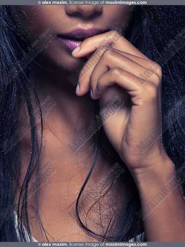 Sensual artistic closeup of young woman mouth biting her finger with sand particles on her face and hair