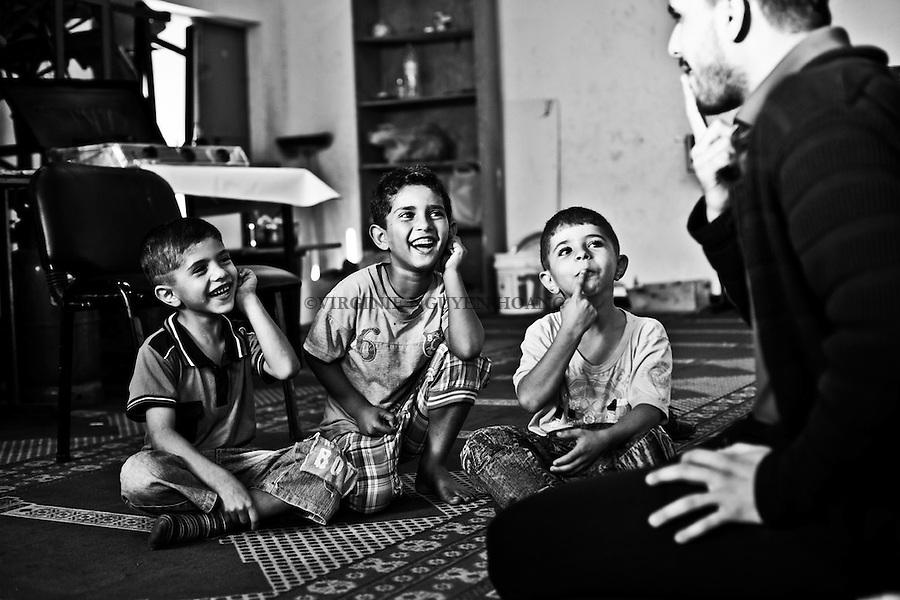 Gaza, Beach Camp: un travailleur social et psychologue pour enfants travaille avec les enfants de Shadi.<br /> <br /> Gaza Beach Camp: a social worker and child psychologist working with Shadi's children.