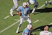 Houston Oilers quarterback Warren Moon (1) looks for a receiver during the game against the Washington Redskins at RFK Stadium in Washington, DC on September 16, 1985.   The Redskins won the game 16 - 13.<br /> Credit: Howard L. Sachs / CNP