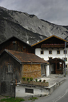Wood stored in barn for winter fuel, next to village house with wooden balcony. Roppen area, Imst district,Tyrol, Austria.