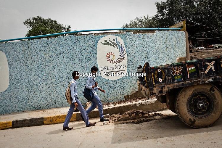 School students walk past the construction site of an underpass leading to the Tyagaraja stadium for the approaching 19th Commonwealth Games 2010 in New Delhi, India.