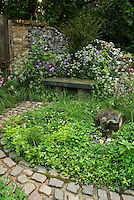 Stone garden bench and stone walkway in circular pattern with lush flowers and plants, old brick wall