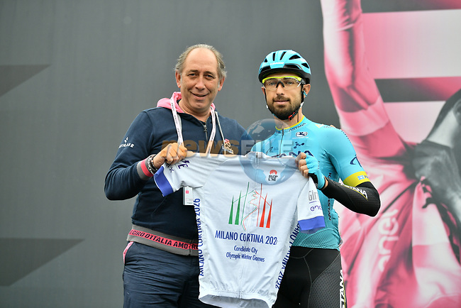 On Sunday's stage Dario Cataldo (ITA) Astana Pro Team was first to pass the special line (26km before the finish) dedicated to Milano Cortina's bid to host the 2026 Winter Olympics. Today he received a special jersey featuring the Milano Cortina 2026 logo presented to him by Giro d'Italia Director Race Director Stefano Allocchio at sign on before Stage 16 of the 2019 Giro d'Italia, running 194km from Lovere to Ponte di Legno, Italy. 28th May 2019<br /> Picture: Massimo Paolone/LaPresse | Cyclefile<br /> <br /> All photos usage must carry mandatory copyright credit (© Cyclefile | Massimo Paolone/LaPresse)