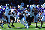 Linfield QB Sam Riddle drops back to pass while Whitworth Linebacker (25) attempts to sack him.