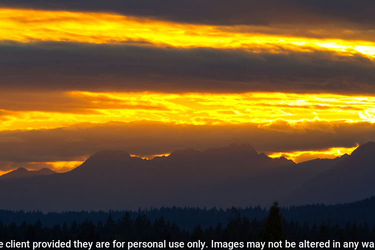 Sun Beams filter the sky near the silhouetted  Olympic mountains in Washington's Olympic National Park. The Olympic Mountains is a year-round destination. In summer, visitors come for views of the Olympic Mountains, as well as for superb hiking.  Jim Bryant Photo. ©2015. All Rights Reserved.