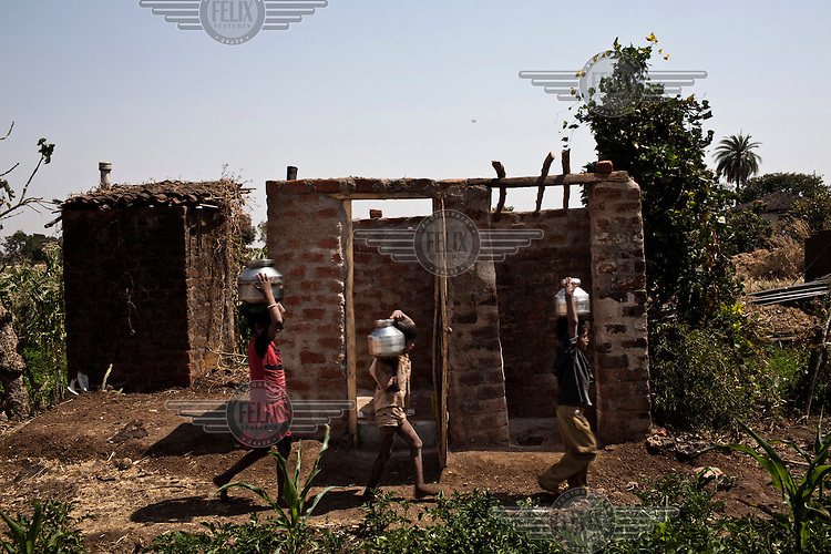 Children carry water vessels past a block of newly constructed toilets in Zitudhana Village.