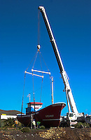Crane unloading fishing boat to be used as decoration on Chaffiras Industrial park. The south of Tenerife, Canary Islands,Spain