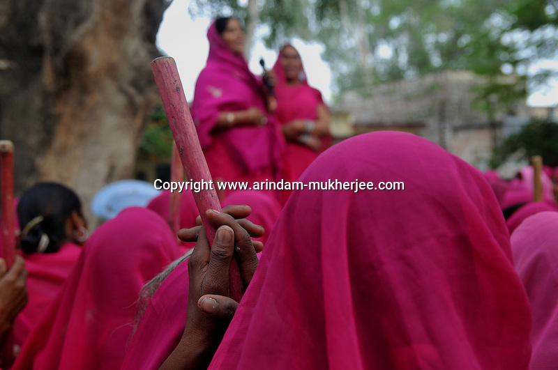 A member of Gulabi Gang with a stick during a meeting. Sampat pal Devi the commander of Gulabi Gang fights for women empowerment, justice and rights among the poor people of Bundelkhand region of Uttar Pradesh. Sampat Pal Devi comes from a poor family in Bundelkhand - the poorest region of India. The region is fraught with abject poverty, gross under development, lack of law and order, and stark casteism in which the Brahmins and other higher caste people treat their low caste brethren with disdain. Out of such situation when Sampat Pal Devi decided to speak up for the poor, she has been winning heart felt gratitude of the poor as well as enmity of the high caste people and grudging respect of the law enforcement officials who used to be largely inactive in these badlands of North India. Initially, she began with helping distressed women - victims of domestic violence and dowry system, but soon started getting other cases of nature of land dispute and under development. She emerged as a fiery leader in 2007, when she beat up the OC of the local police station while demanding release of a dalit woman kept locked up in the cell for thirteen days without being charged with a case.Today, she has a huge fan following of some 25 hundreds of thousands of women (spread across 8 districts of the state of UP) who have come to be known as Gulabi Gang or Pink Vigilante Women for their vibrant pink sarees - the costume of the gang; and fiery nature of dealing with injustice. When verbal negotiations for justice fail they resort to beating up. Sampat Devi is viewed as a messiah with the promise of bringing back law and order for the poor, in these mafia troubled areas. Today, perpetrators are simply scared of her as she does not hesitate to challenge law and order and even system - to win justice for the poor. More complaints related to domestic violence and other problems are registered now with the police than they ever used to be. She being one of the Other Backward Caste peop