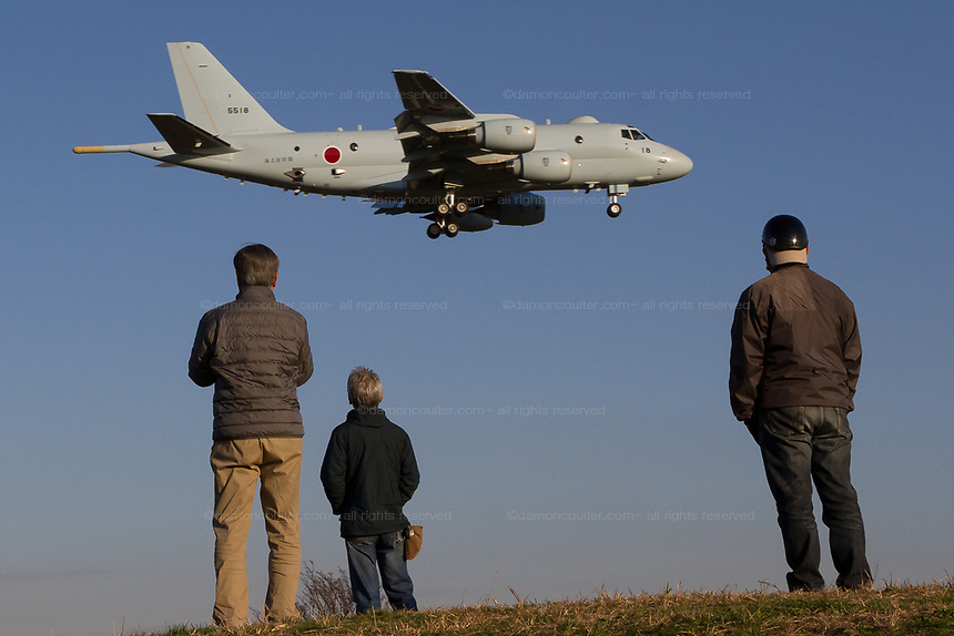 Older Japanese men watch a Kawasaki P1 Maritime patrol aircraft with the Japanese Self Defence Force (JSDF) practice landing at Atsugi Air base  near Yamato, Kanagawa, Japan. Friday November 30th 2018