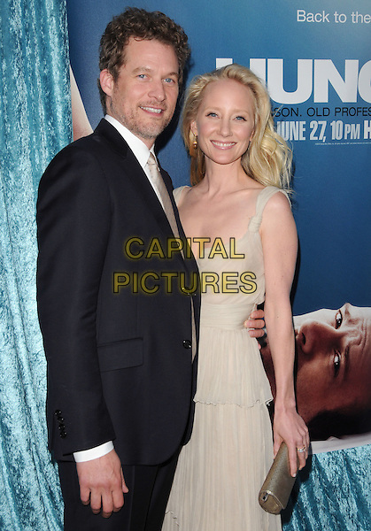 JAMES TUPPER & ANNE HECHE.The HBO Premiere of 2nd Season of Hung held at Paramount Picture Studios in Hollywood, California, USA..June 23rd, 2010.half length black suit white cream dress beige layers layered sheer gold clutch bag couple stubble facial hair.CAP/RKE/DVS.©DVS/RockinExposures/Capital Pictures.