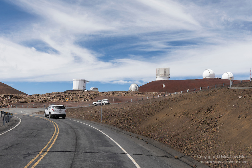 Mauna Kea, Big Island of Hawaii, Hawaii; view of the paved road leading up to the summit of the Mauna Kea Observatories (MKO), with the (left to right) Caltech Submillimeter Observatory, Subaru Telescope and Keck 1 and 2 Telescopes in the background, currently there are 13 independent multi-national astronomical research facilities located on the summit. Mauna Kea's altitude and isolation in the middle of the Pacific ocean make it an ideal location for astronomical observation.