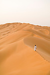 A man walks alone on the sand dunes of the Empty Quarter, Ar Rub Al Khali, Oman.