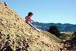 Emeryville, CA  Girl, six-years-old exultantly playing in construction debris at waterfront site  MR