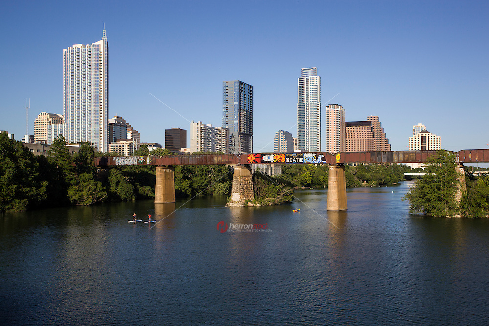 """Austin's """"Let's Pretend We're Robots"""" and """"Focus One Point And Breathe"""" graffiti murals painted across the rail bridge over Lady Bird Lake stand as the gateway to the growing Austin Skyline."""