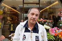 Vasiliy, a Russian business visitor to Nice, poses for the photographer in front of a flower stall in Rue Paradis, Nice, France, 28 April 2012