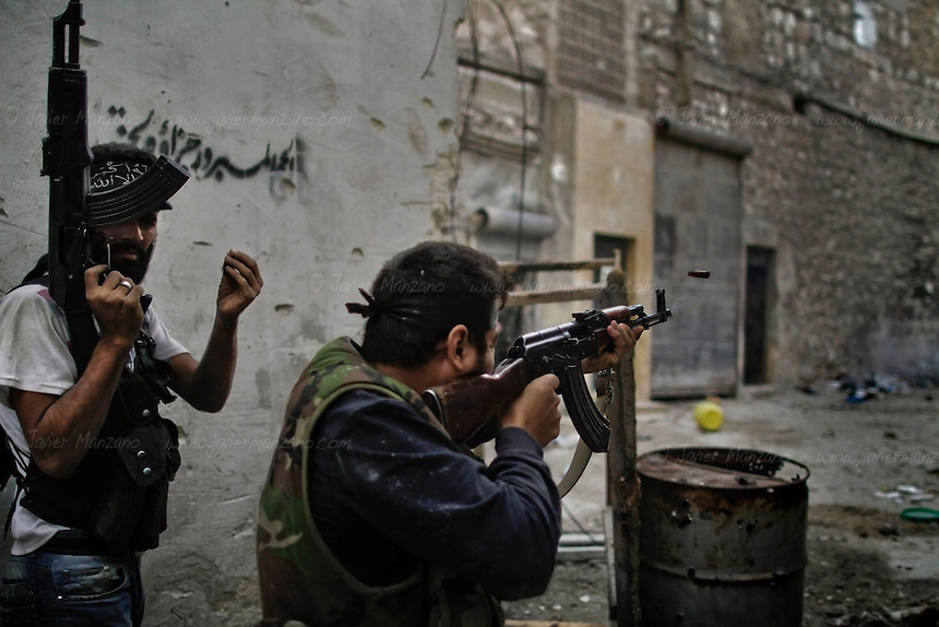 Free Syria Army (FSA) soldiers battle loyalist soldiers in the Askar neighborhood of Aleppo. FSA soldiers used a DShK 12.7mm machine gun in an attempt to dislodge a regime sniper positioned at one of the buildings overlooking two main roads. ..© AFP/Javier Manzano