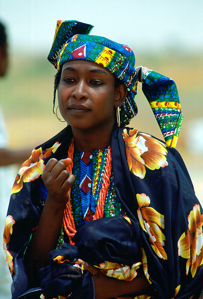 Nigerian woman in brightly coloured clothes and with the traditional face markings.