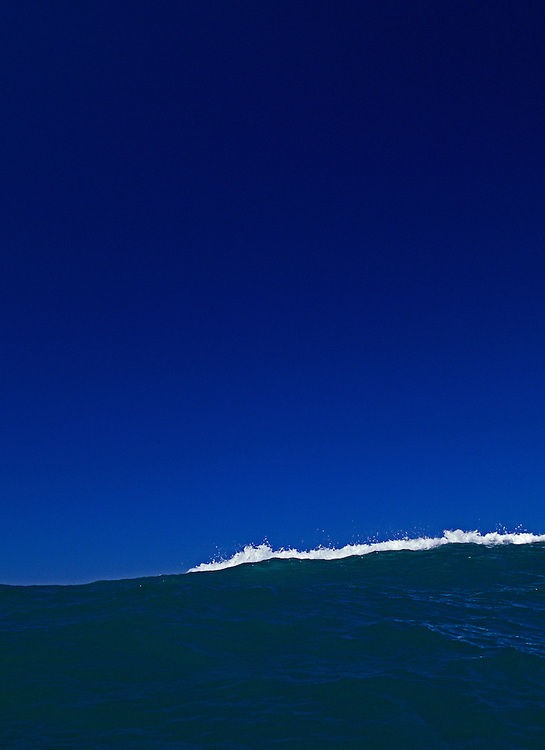 Minimalistic image of a breaking wave in the surf,