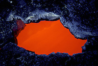 Red hot lava forms a pool in a lava tube window at  Hawaii Volcanoes National Park.