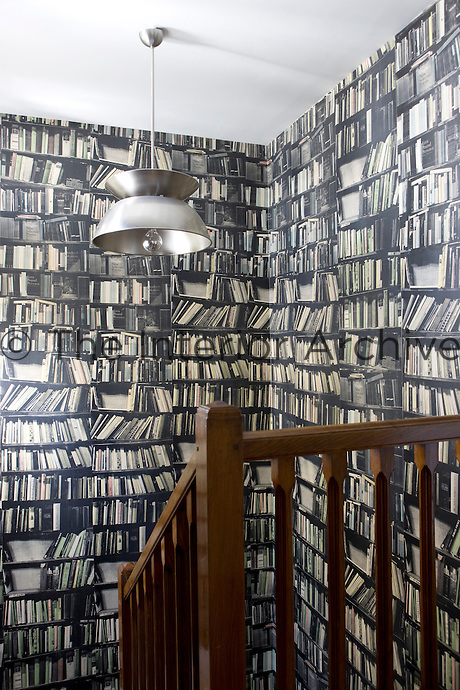 The stairwell is lined in a wallpaper with a vintage trompe l'oeil design comprising rows of library shelves