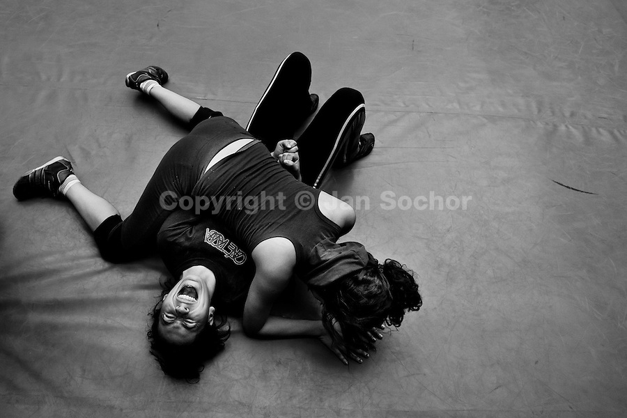 "A female Lucha libre wrestler locks her sparring partner in a hold during the training classes at a combat sports gym in Mexico City, Mexico, 28 April 2011. Lucha libre, literally ""free fight"" in Spanish, is a unique Mexican sporting event and cultural phenomenon. Based on aerial acrobatics, rapid holds and the use of mysterious masks, Lucha libre features the wrestlers as fictional characters (Good vs. Evil). Women wrestlers, known as luchadoras, often wear bright shiny leotards, black pantyhose or other provocative costumes. Given the popularity of Lucha libre in Mexico, many wrestlers have reached the cult status, showing up in movies or TV shows. However, almost all female fighters are amateur part-time wrestlers or housewives. Passing through the dirty remote areas in the peripheries, listening to the obscene screams from the mainly male audience, these no-name luchadoras fight straight on the street and charge about 10 US dollars for a show. Still, most of the young luchadoras train hard and wrestle virtually anywhere dreaming to escape from the poverty and to become a star worshipped by the modern Mexican society."