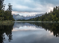 Southern Alps reflecting in Lake Matheson after fresh snowfall at sunrise, Westland Tai Poutini National Park, UNESCO World Heritage Area, West Coast, New Zealand, NZ