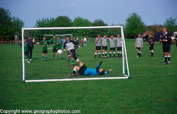 AF5GM8 Children's football tournament. View of goalkeeper from behind the net. Penalty shoot out.