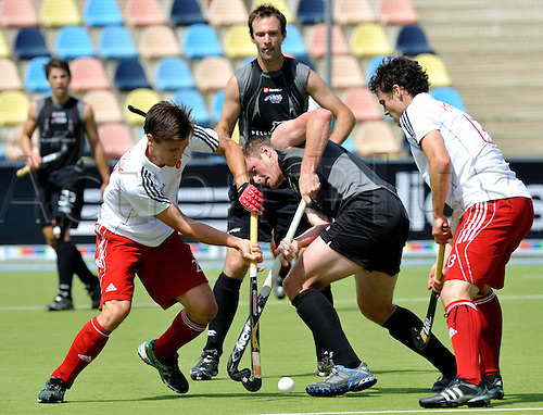 England's Iain Mackay (L)and New Zealand's Bradley Shaw (C) going for the ball during their Champions Trophy match in Moenchengladbach, Germany, 07 August 2010. England defeated New Zealand with 4-3.