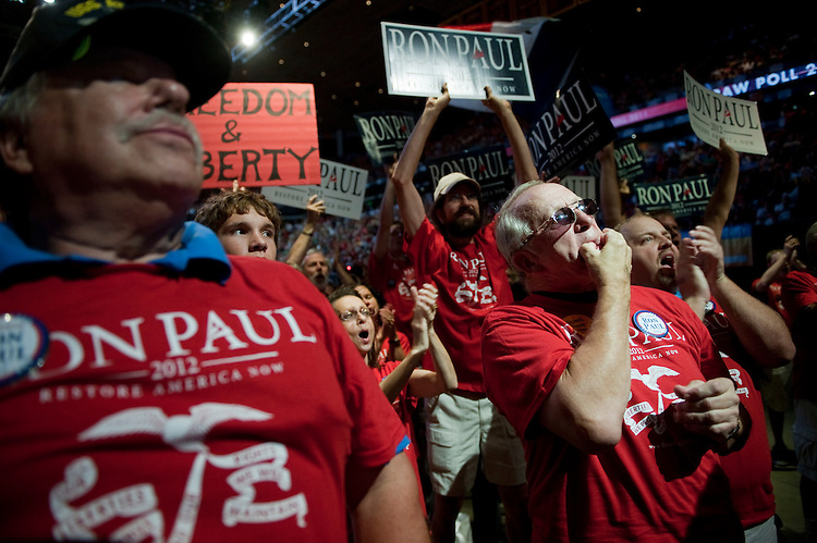 UNITED STATES - AUGUST 13:  Terry Mickle, right, of Waukee, Iowa, applauds for Republican presidential candidate Ron Paul in the Hilton Coliseum at Iowa State University during candidate speeches at the Ames Straw Poll in Ames, Iowa.  (Photo By Tom Williams/Roll Call)