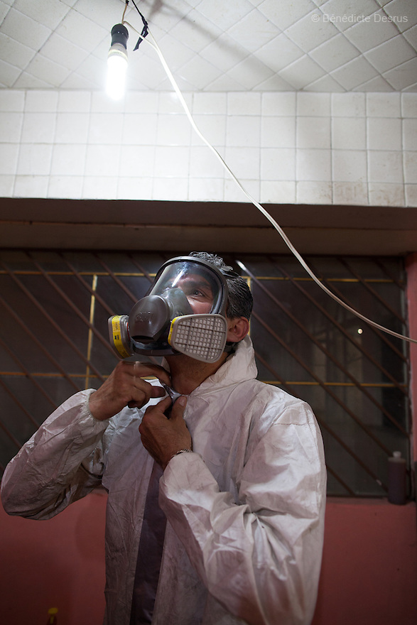 """Donovan puts on his Hazmat suit before beginning a forensic cleaning in Iztacalco, Mexico on October 16, 2015. The decomposed body of a man in his 60s was found in his bedroom a number of days after he died of a heart attack – although the deceased's own family members were unsure exactly how long he had been there. The victim's family remarked that the police had made unfounded insinuations against them, and had sought bribes. As a result they found Donovan's discretion and professionalism to be a welcome contrast. Donovan Tavera, 43, is the director of """"Limpieza Forense México"""", the country's first and so far the only government-accredited forensic cleaning company. Since 2000, Tavera, a self-taught forensic technician, and his family have offered services to clean up homicides, unattended death, suicides, the homes of compulsive hoarders and houses destroyed by fire or flooding. Despite rising violence that has left 70,000 people dead and 23,000 disappeared since 2006, Mexico has only one certified forensic cleaner. As a consequence, the biological hazards associated with crime scenes are going unchecked all around the country. Photo by Bénédicte Desrus"""