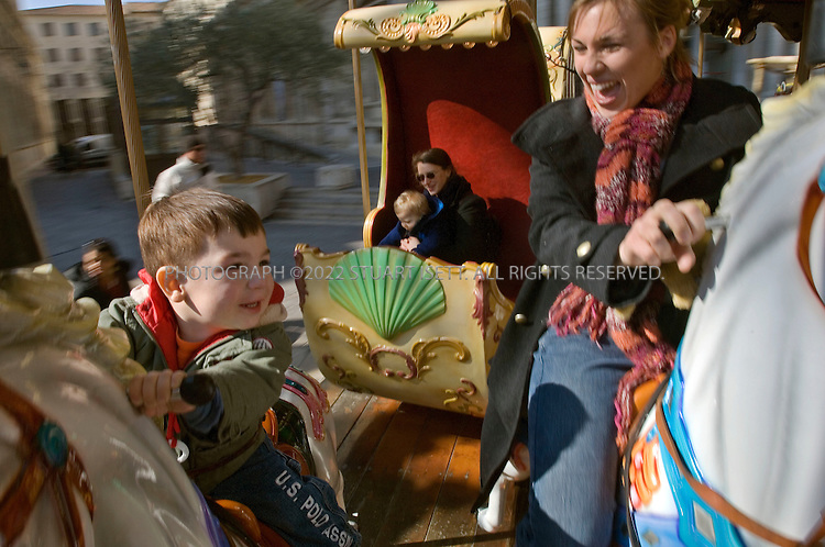 2/26/2006--Avignon, France..2 year old Sean Young, from Illinois, rides the antique merry-go-round, Carrousel Belle Epoque on the Place de l'Horloge, with his mother. The ride costs 2 euros and operates between 1:00 pm and 8:00 pm..Photograph By Stuart Isett.All photographs ©2005 Stuart Isett.All rights reserved.